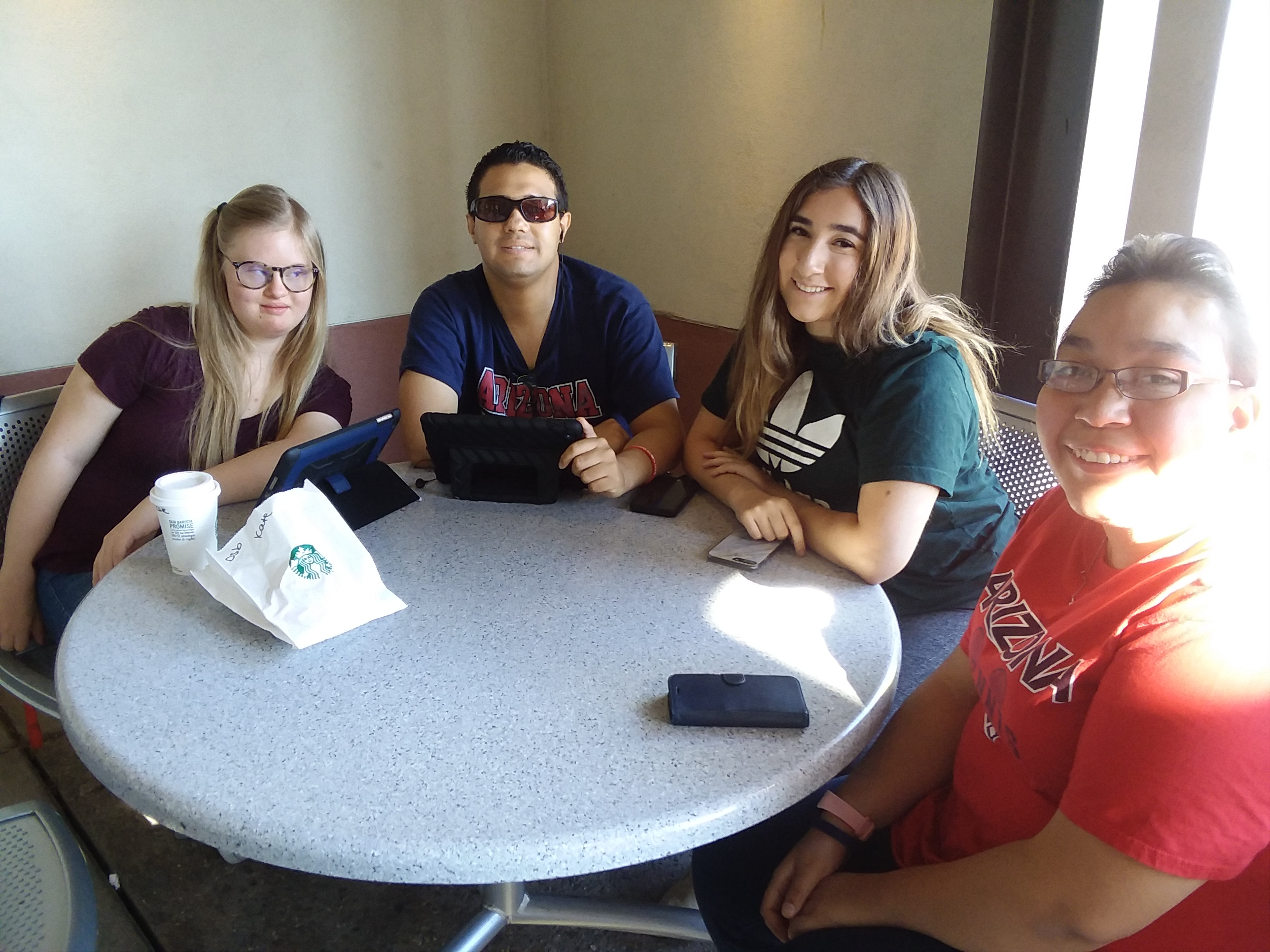 group of four students sitting at table