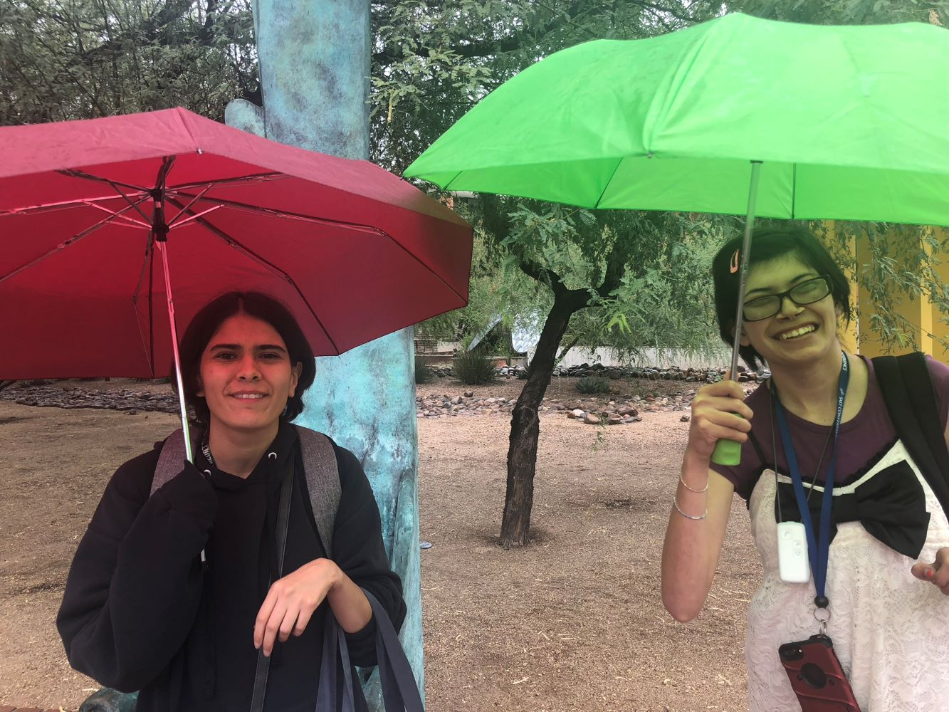 two students smiling outside holding open umbrellas