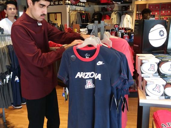 A student working at the UArizona bookstore with a peer mentor looking on as support
